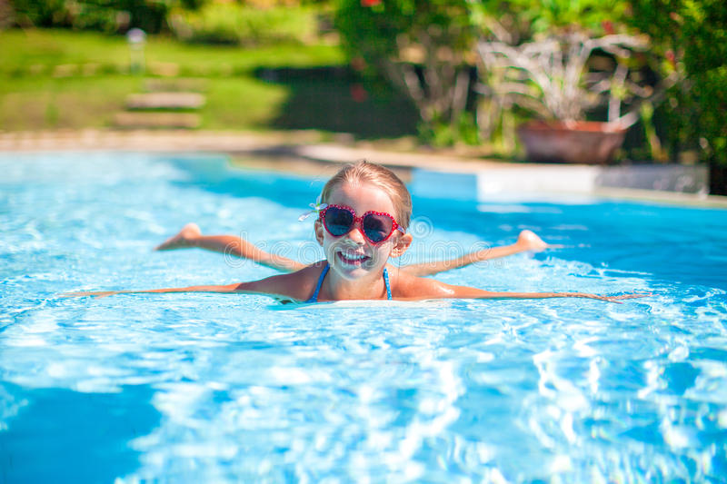 Little adorable happy girl swims in the swimming. Pool. This image has attached release royalty free stock photos