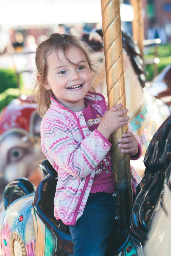 Little adorable smiling girl riding a horse on roundabout carousel at funfair stock photos