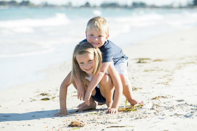Little adorable and sweet siblings playing together in sand beach with small brother hugging his beautiful blond young sister enjo stock images