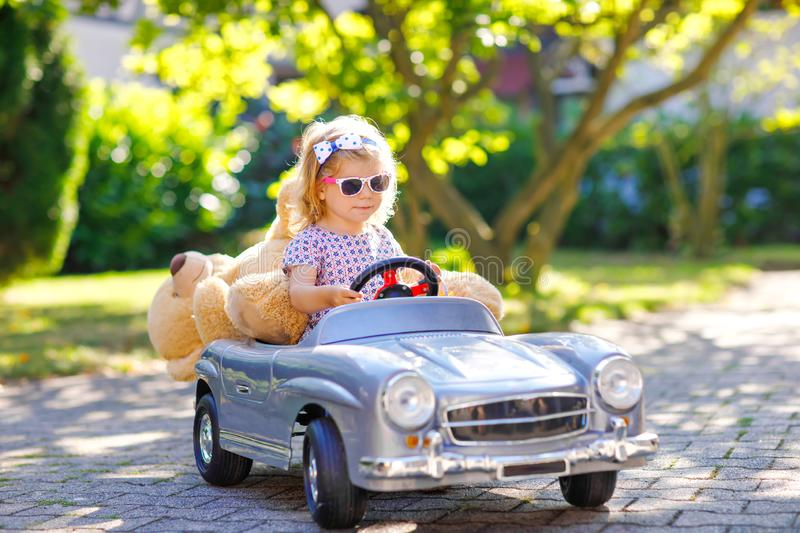 Little adorable toddler girl driving big vintage toy car and having fun with playing with plush toy bear, outdoors royalty free stock photo