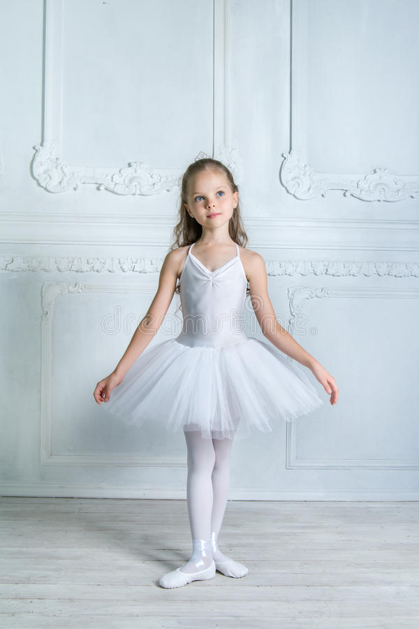 A little adorable young ballerina isposing on camera in the interior studio royalty free stock photos