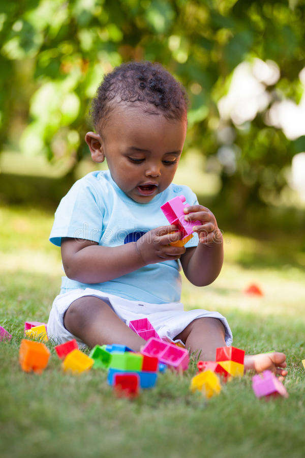 Little african american baby boy playing in the grass stock image
