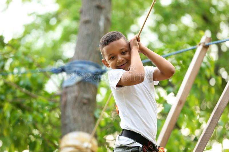 Little African-American boy climbing in adventure park stock image