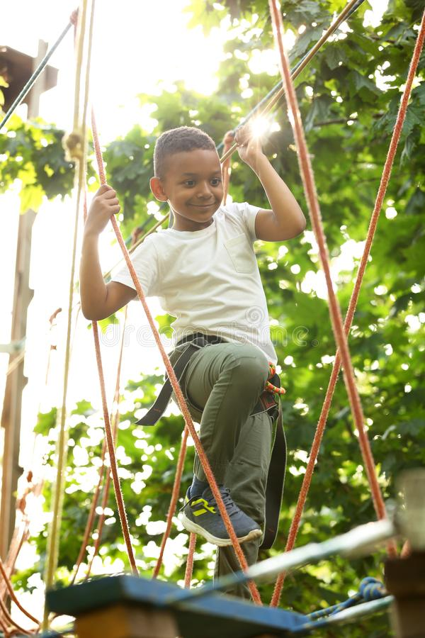 Little African-American boy climbing in adventure park royalty free stock image