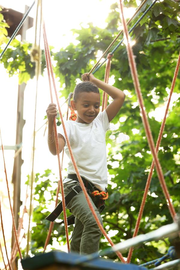 Little African-American boy climbing in adventure park royalty free stock photography