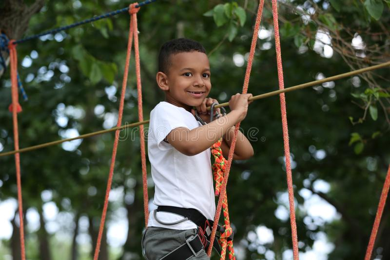 Little African-American boy climbing in adventure park royalty free stock photo