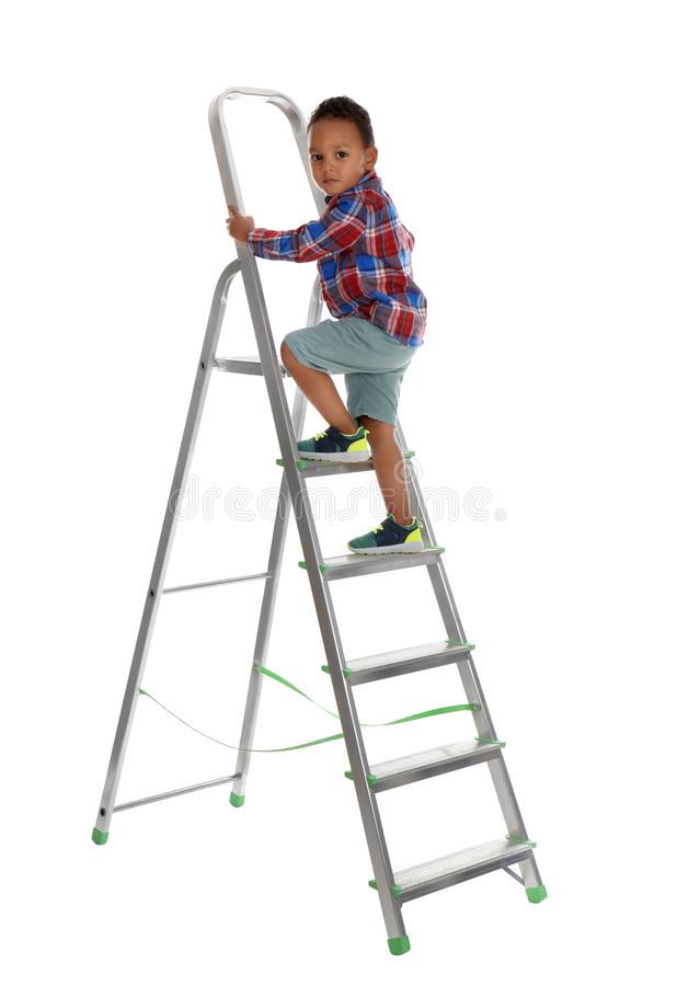 Little African-American boy climbing up ladder on background. Danger at home stock photo