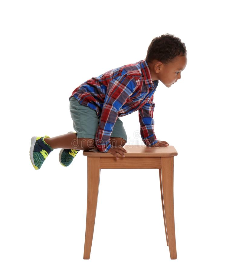 Little African-American boy climbing up  on white background. Danger at home royalty free stock photos