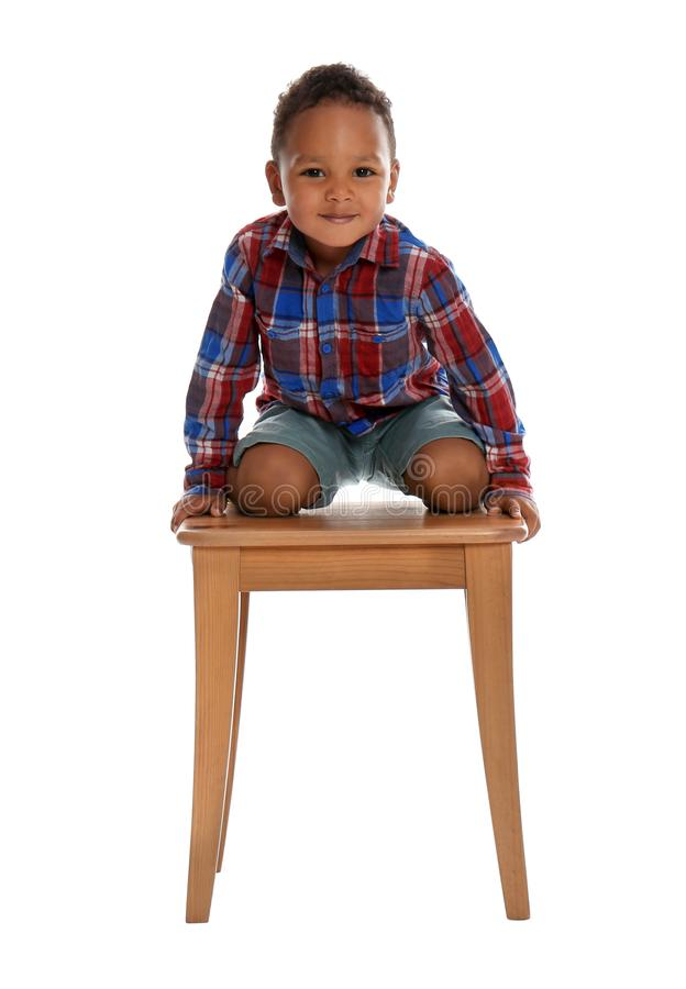 Little African-American boy climbing up stool on white background stock photography