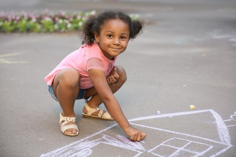 Little African-American child drawing house with chalk. On asphalt stock photo