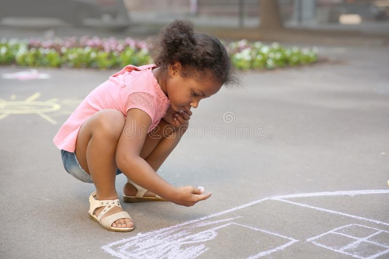 Little African-American child drawing house with chalk. On asphalt royalty free stock images