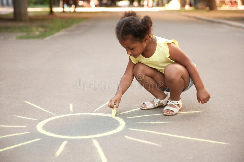 Little African-American child drawing sun with chalk. On asphalt royalty free stock photos