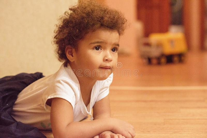 Little african american cute girl laying on floor with smile emotion on face isolated on white background royalty free stock photos