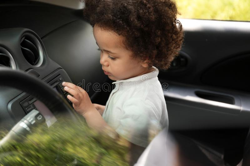 Little African-American girl alone inside car stock photography