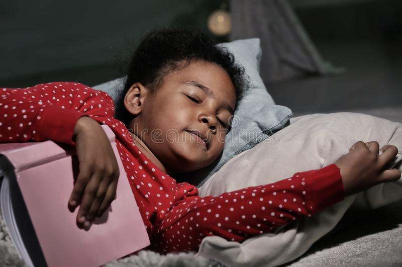Little African-American girl with book sleeping in bed stock images