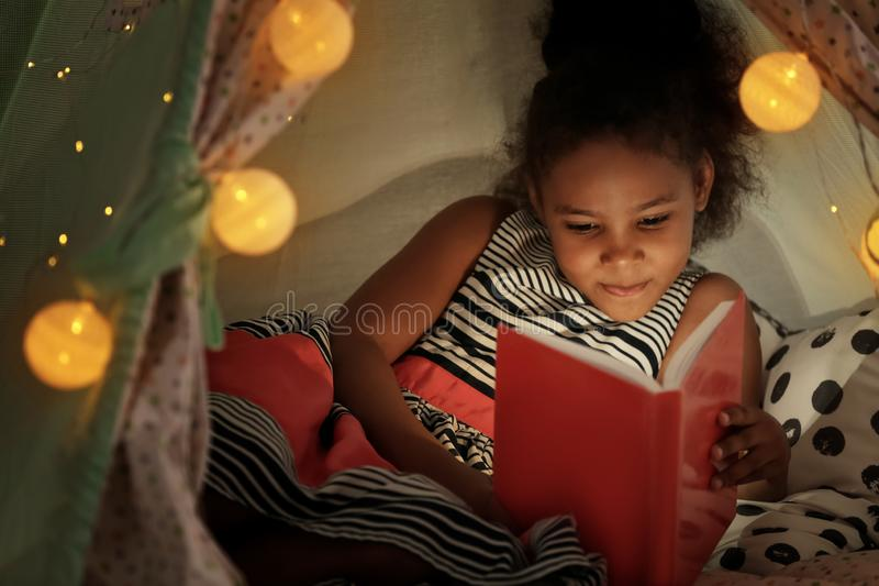 Little African-American girl reading bedtime story in hovel royalty free stock images