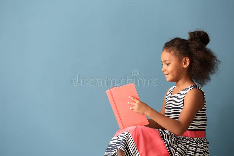Little African-American girl reading book on color background stock image