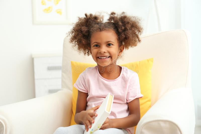 Little African American girl sitting in armchair and reading book in room stock image