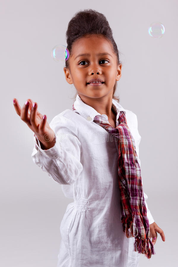 Little African Asian Girl Blowing Soap Bubbles Royalty Free Stock Photo