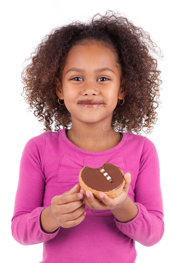 Little African Asian girl eating a chocolate cake stock photo