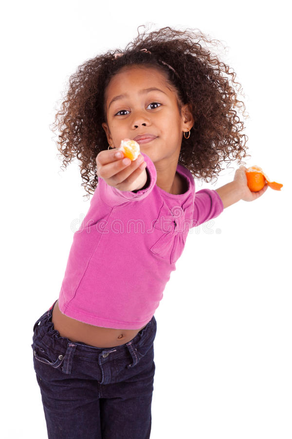 Little African Asian girl sharing a tangerine stock image