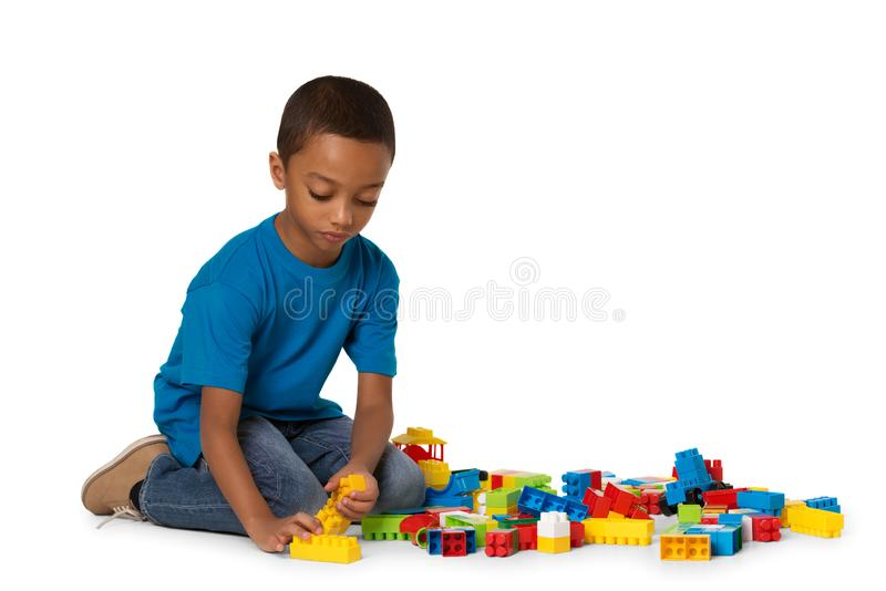 Little african boy playing with lots of colorful plastic blocks indoor. Isolated stock image