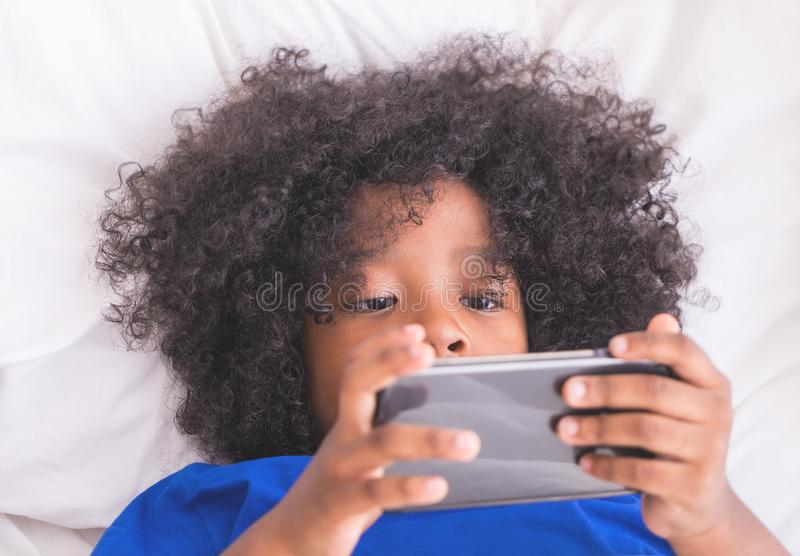 Little kid is playing with smartphone on bed stock photography