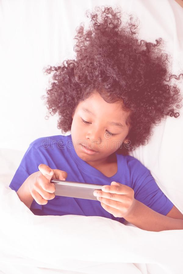 Little African kid playing with smartphone on bed stock photos