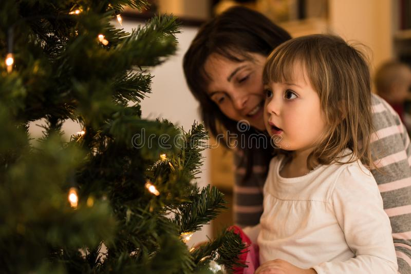Little amazed girl with her mother at home stock image