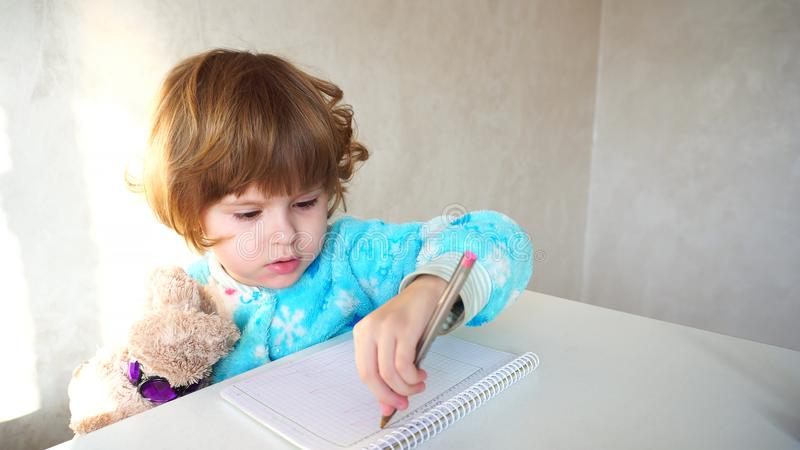 Little american girl with pink pen learns draw. stock photos