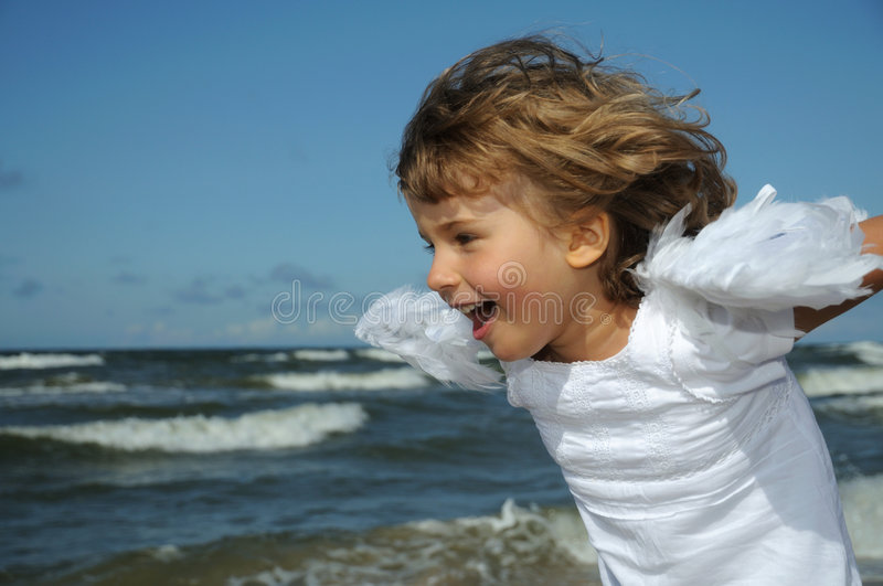 Little angel on the beach. Little girl with angel wings playing on the beach royalty free stock photo