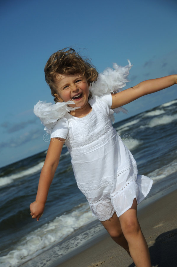 Little angel on the beach. Little girl with angel wings playing on the beach stock photography