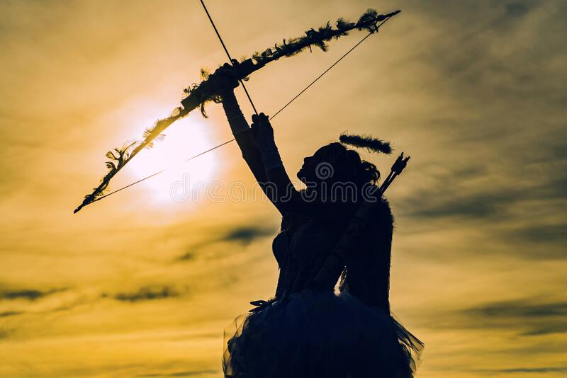 Little angel girl against sunny sky. Teen angel girl archer on sunset. Silhouette of a cupid. Side view of teen girl stock images