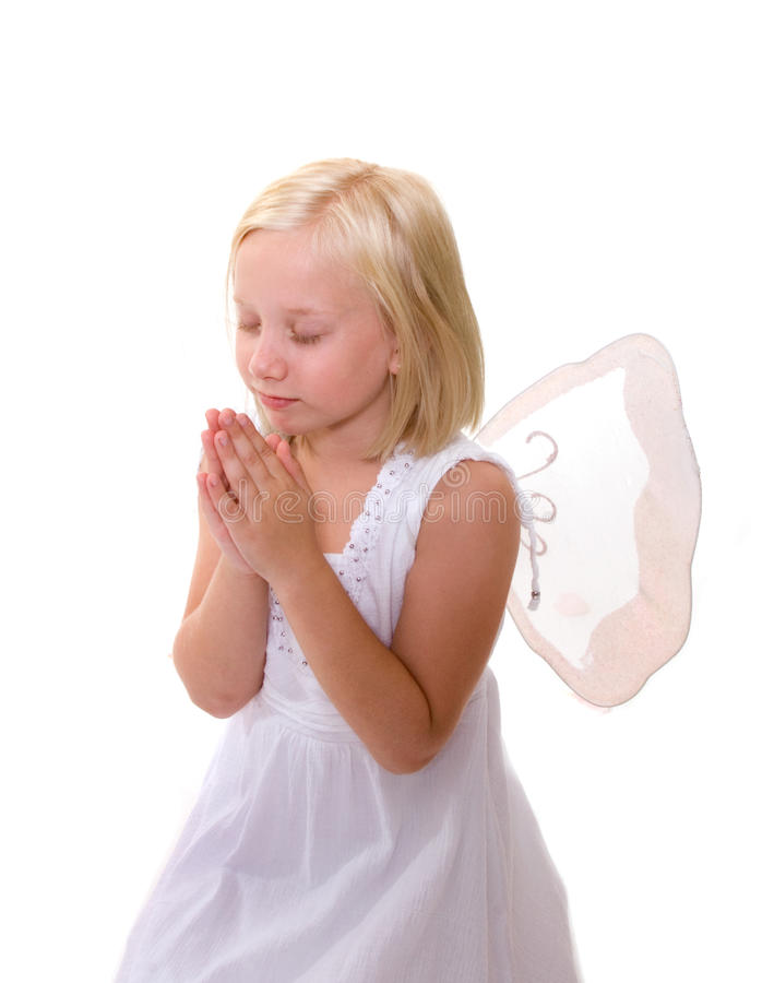 Little Angel: Girl praying, wearing wings. Little blonde girl with her hands together, eyes closed, looks like she is praying. She is wearing a white dress with royalty free stock photos
