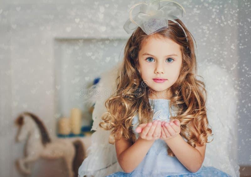 Little angel in light blue dress blowing snow stock image