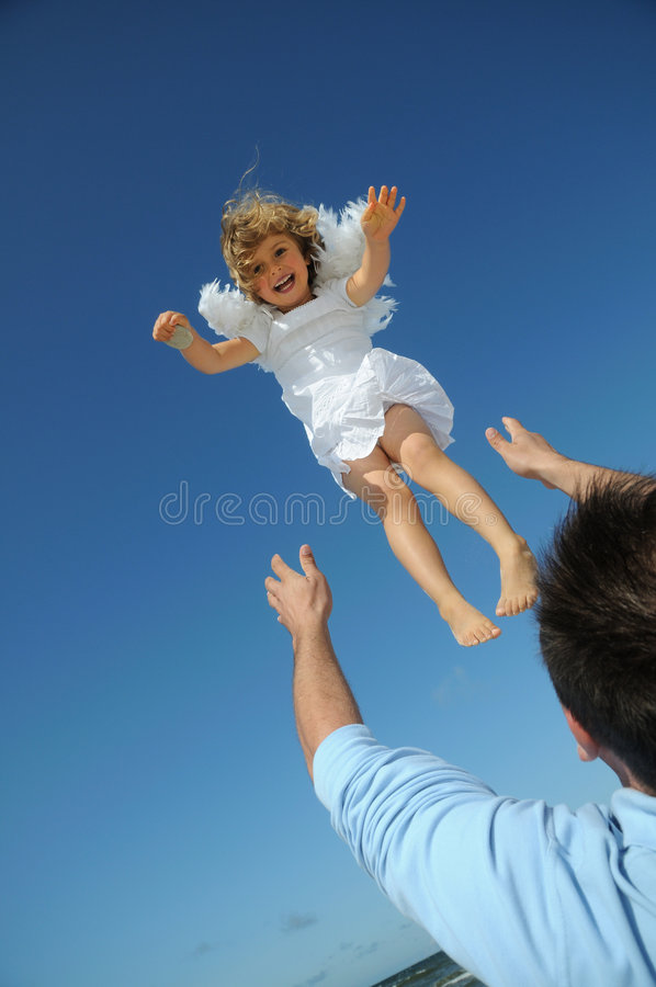 Little angel on the sky. Flying little angel on the beach