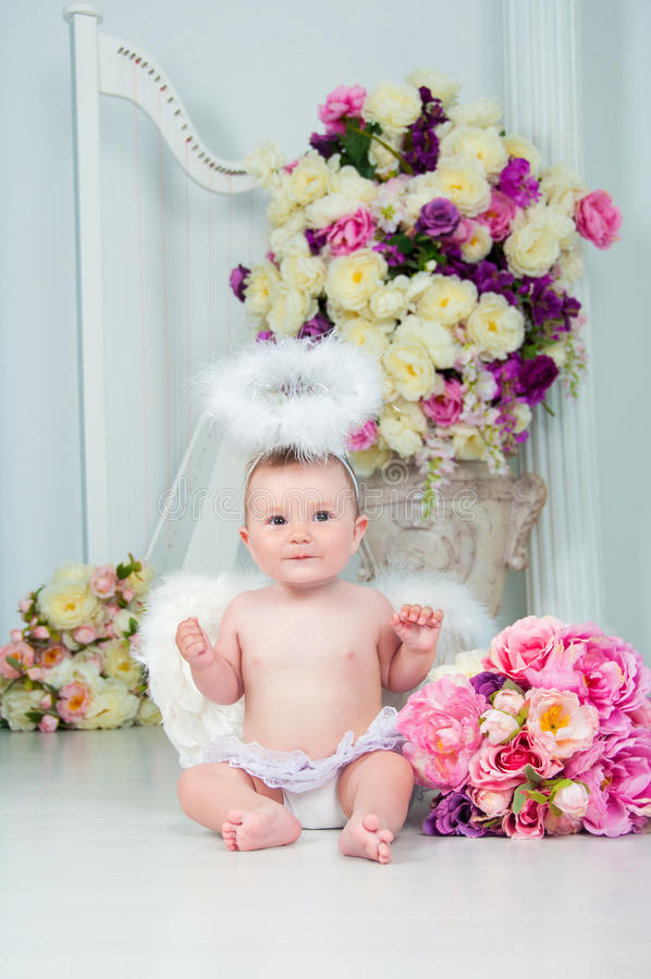 Little angel smiling and happy sitting on the background of flowers and harp royalty free stock image