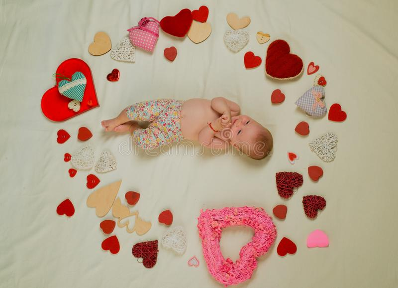 Little angel for valentine. Family. Child care. Small girl among red hearts. Love. Portrait of happy little child royalty free stock photo
