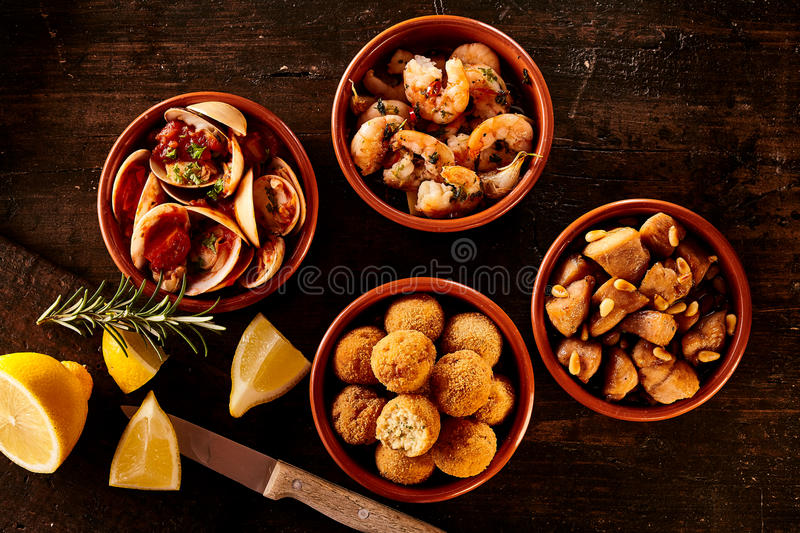 Little appetizer bowls with knife and lemon. Four little Spanish style seafood appetizer bowls next to knife, rosemary sprigs and lemon slices over wooden table stock image