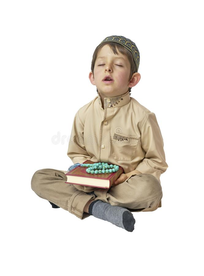 Little arabic boy praying and holding holy Koran with prayer beads on white background. Muslim Arabic boy praying on white background stock photos