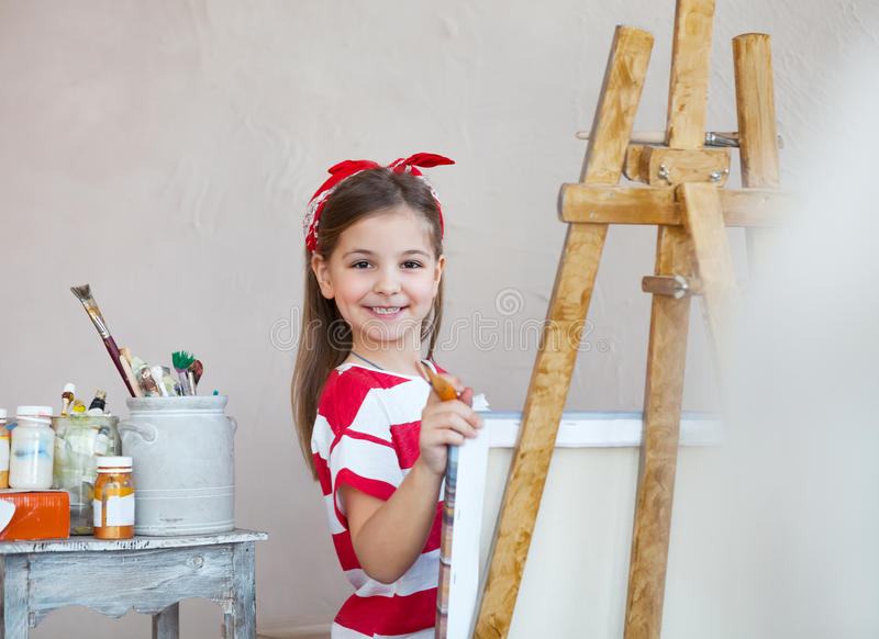 Little artist girl holding a paintbrush and looking over a canvas royalty free stock photo