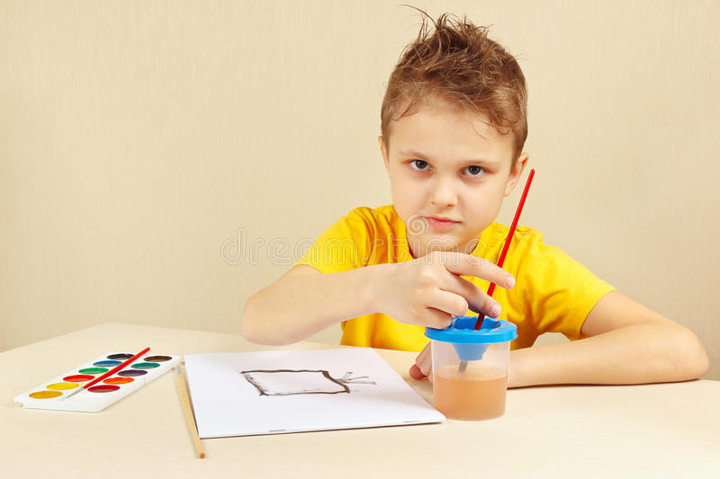 Little artist in yellow shirt painting with watercolors. Little artist in a yellow shirt painting with watercolors stock images
