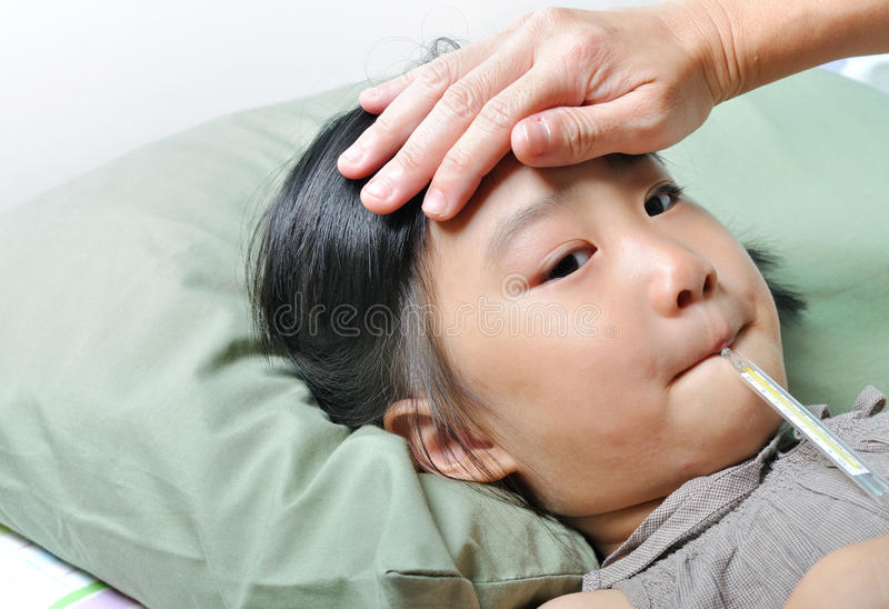 Little asain sick girl with temperature in mouth and caring moth stock photo