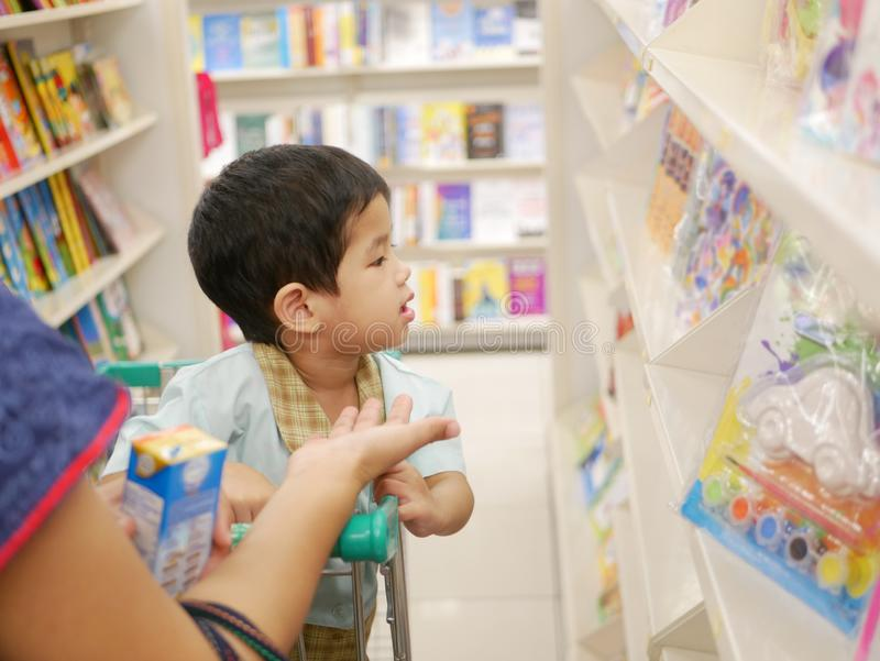 Little Asian baby picking a book at a book store together with her mother royalty free stock photos