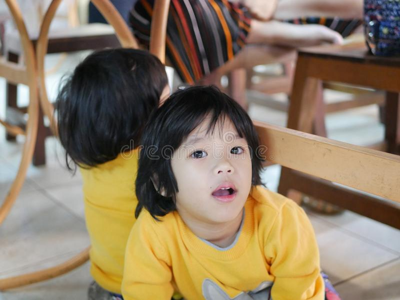 Little Asian baby girlห sitting and playing / exploring with her younger sister under a dinning table at a restaurant stock photo