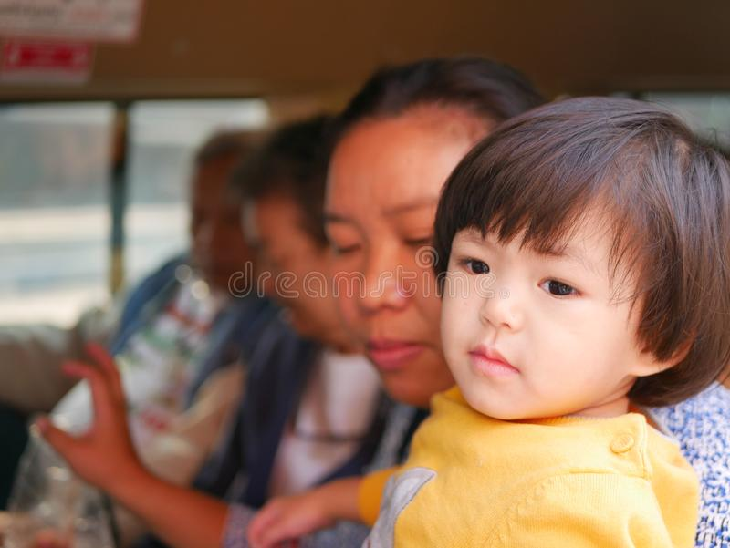 Little Asian baby girl being carried and getting ready for a long trip with her family. Traveling with toddler stock photo