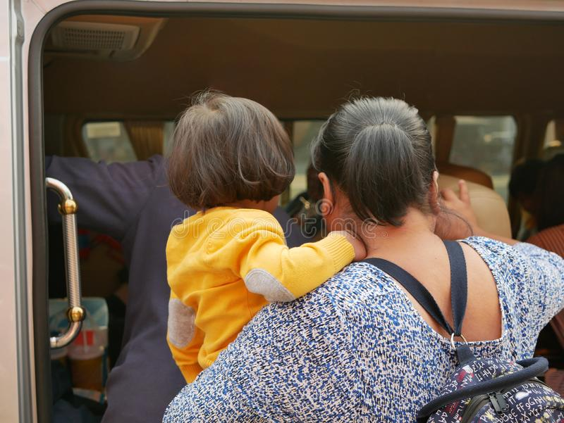 Little Asian baby girl being carried by her auntie, about to get into a van for a long family trip.  stock images