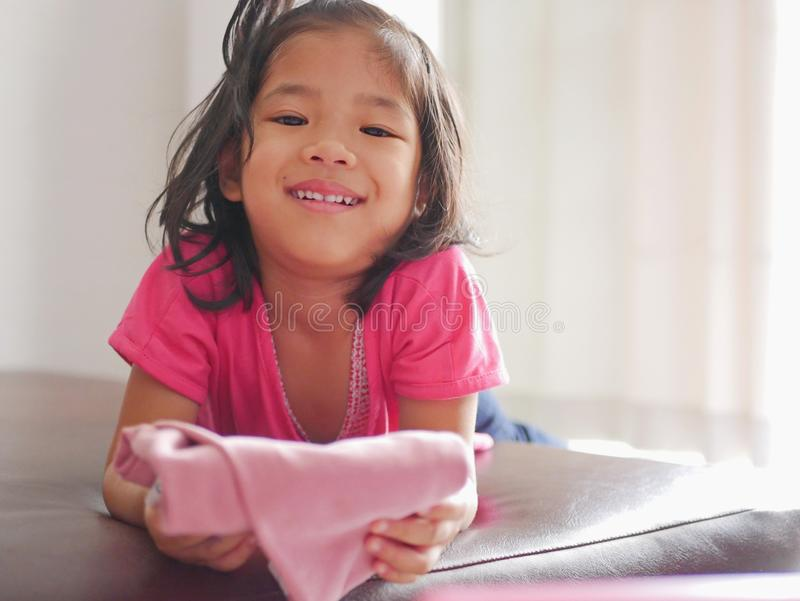 Little Asian baby girl being happy, with big smile, as she just successfully folded her own pants. Children help doing household chores stock image