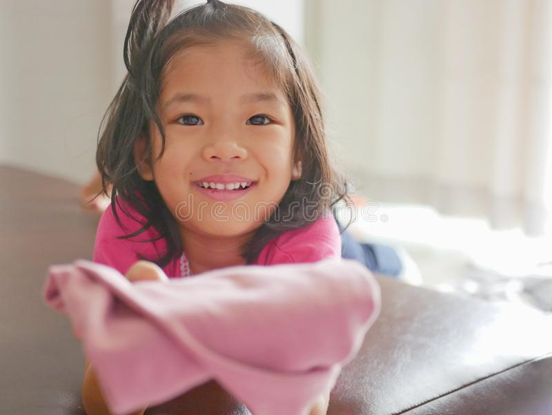 Little Asian baby girl being happy, with big smile, as she just successfully folded her own pants. Children help doing household chores royalty free stock photography
