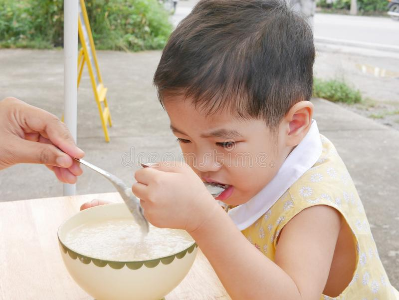 Little Asian baby girl eating hot rice porridge by herself royalty free stock photos